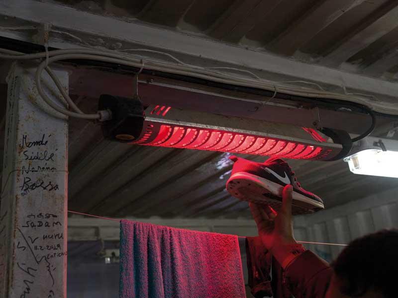 En person håller upp en sko mot en värmelampa.