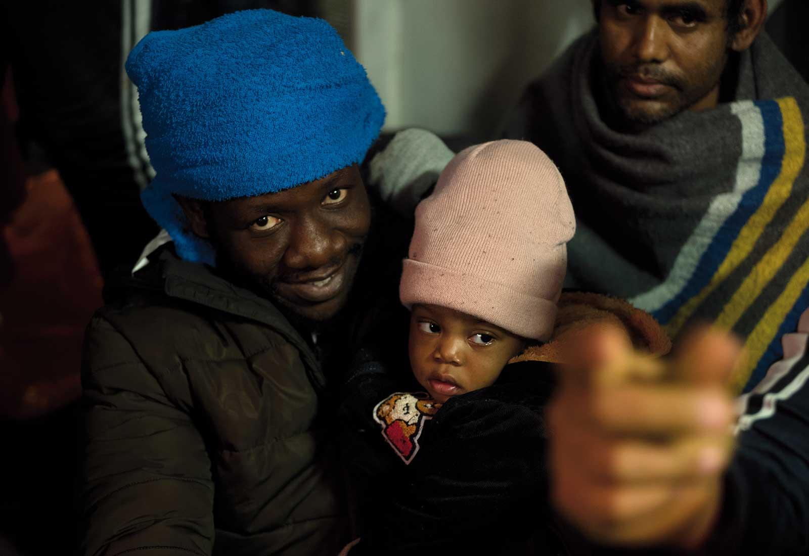 Jolly har virat den blå handduken runt huvudet. Han bär sin dotter i famnen.