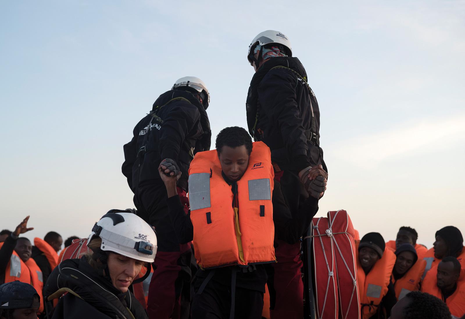 Två livräddare i hjälm hjälper en migrant.