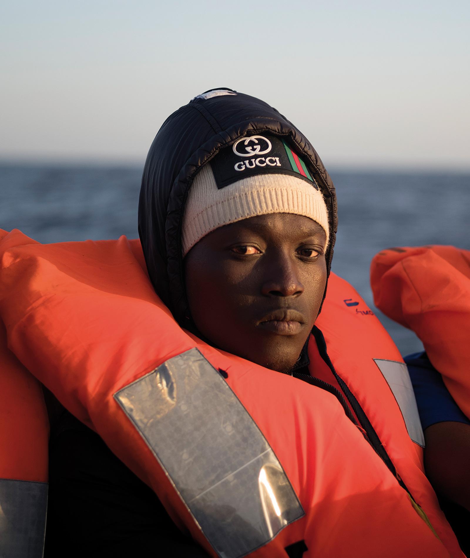 Ibrahima tittar in i kameran. Han har mössa och flytväst.
