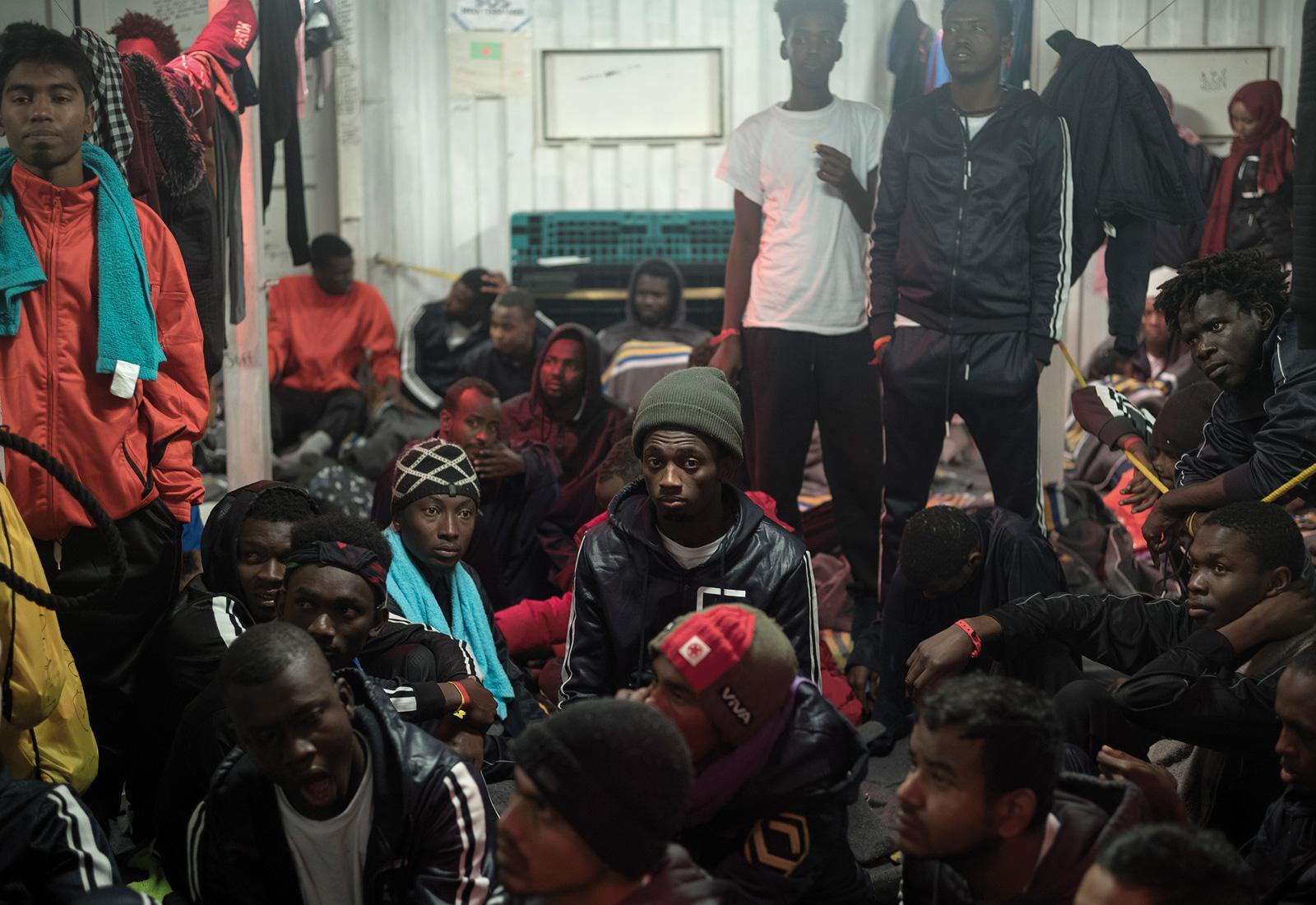 En folksamling. Personer med jackor och mössa lyssnar.