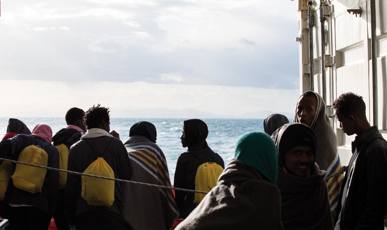 En samling med människor blickar ut över havet.