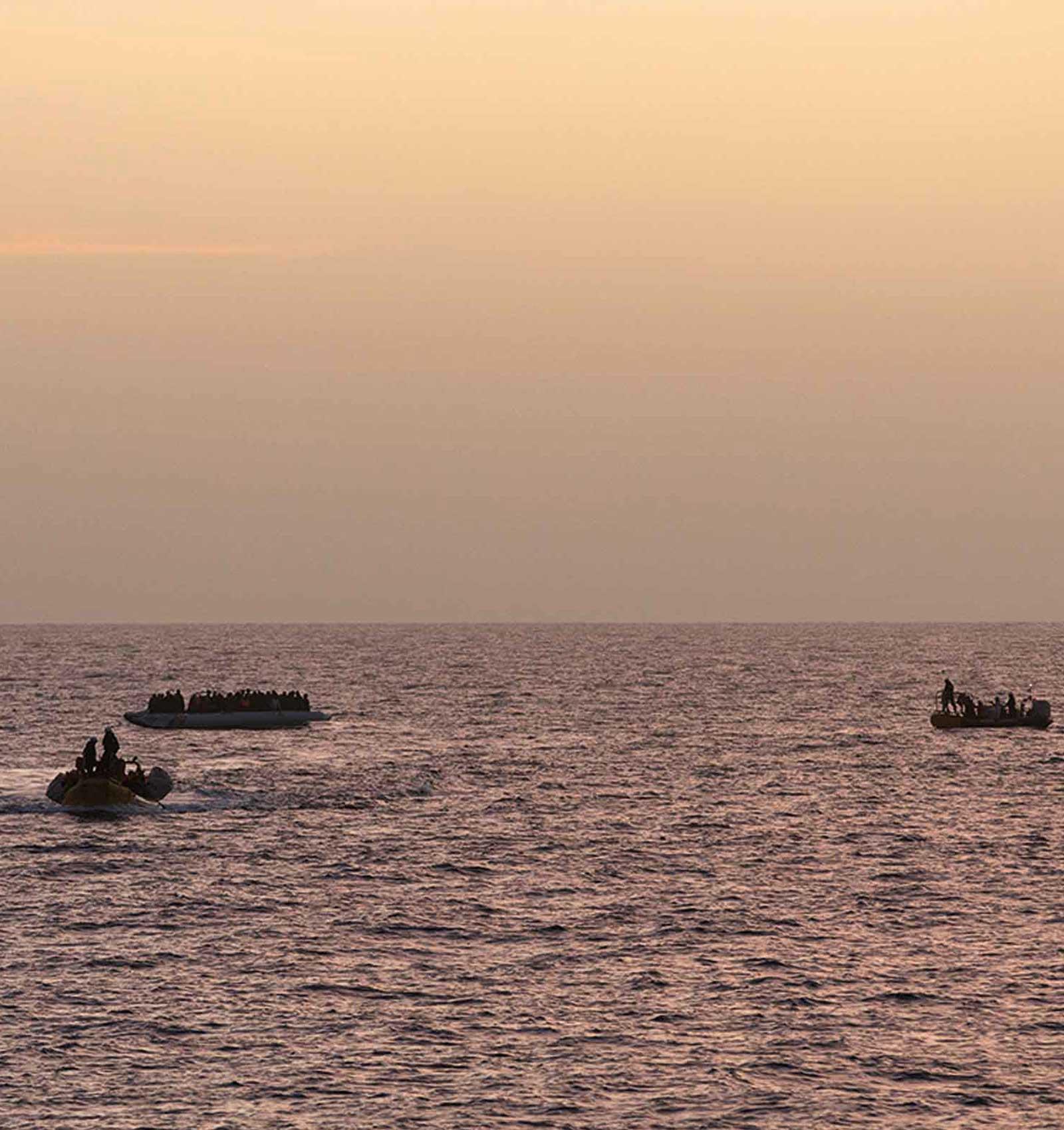 Tre båtar syns på havet, i solnedgången