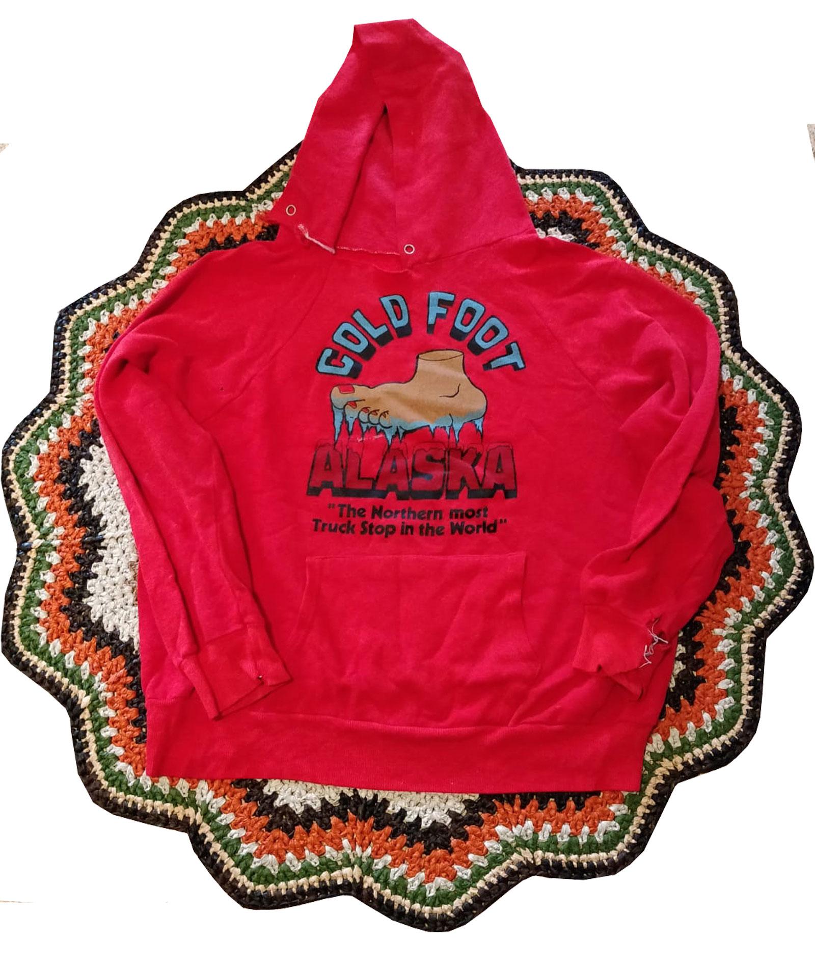 En röd luvtröja med ett motiv tryckt på ryggen – en infrusen fot och texten Cold Foot Alaska.