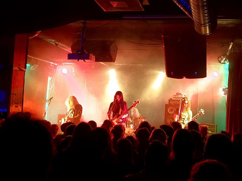 Ett band spelar på scenen. Tre personer har gitarr och bas, en trummis bakom.