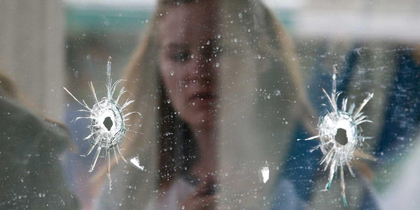 En kvinna studerar två skotthål i en glasruta.