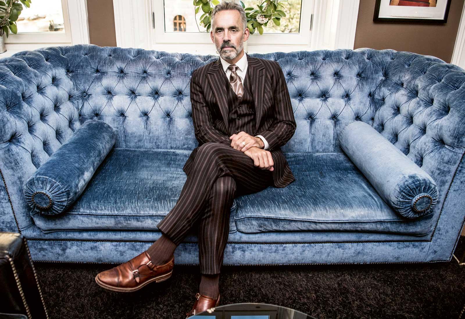 Jordan B. Peterson, i klädd en brun kostym med kritstrecksränder, i en stor blå soffa.